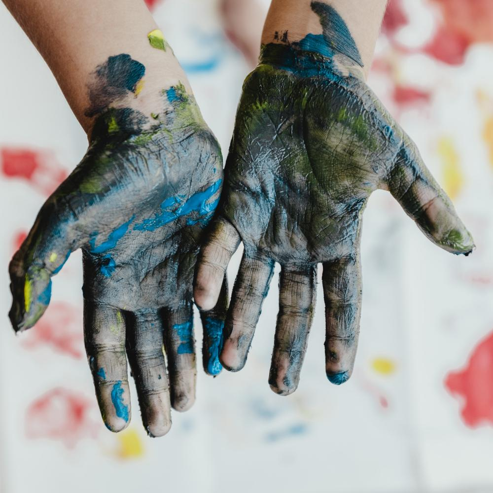 child's hands covered in paint